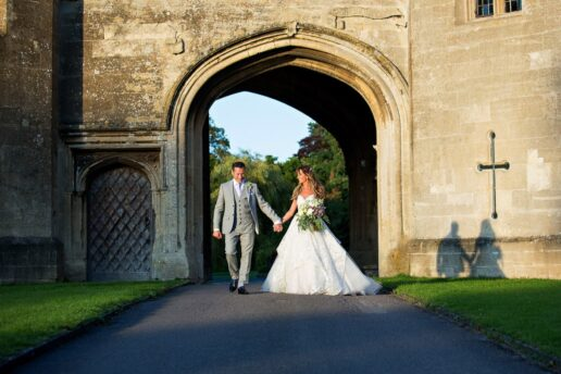 wedding couple walking in front of the gate at thornbury castle