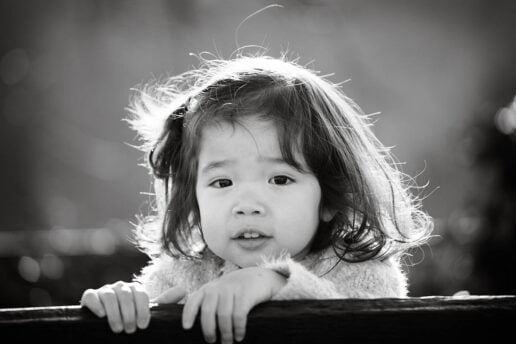 black and white image of little asian girl backlit by sun