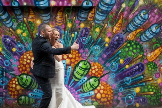 wedding couple laughing in front of vivid and colourful graffiti wall