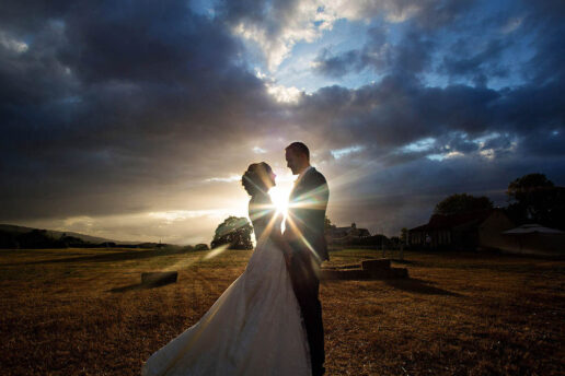 wedding couple facing each other with a sun setting and dramatic sun behind them