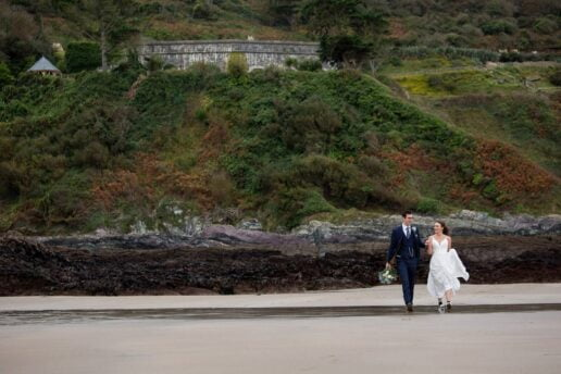 bride and groom walking on the beach with the polhawn fort wedding venue in the background